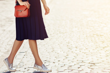 Elegant outfit. Fashionable woman walking in street, holding small red stylish leather bag. Model wearing blue skirt, silvery slippers shoes. City lifestyle. Sunny day. Copy, empty space for text