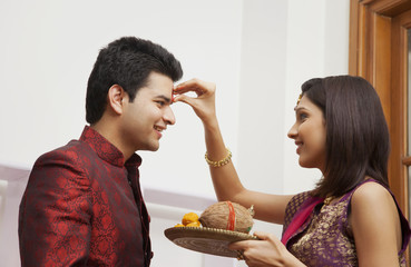 Woman putting tikka on a mans forehead