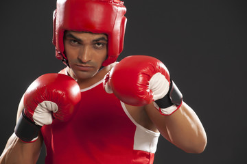 Portrait of an Indian male boxer wearing gloves and head protector against black background