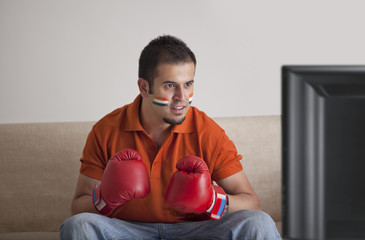 Young man in casuals with painted face wearing boxing gloves watching television at home