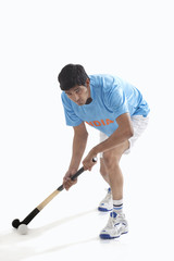 Man in sportswear playing hockey isolated over white background