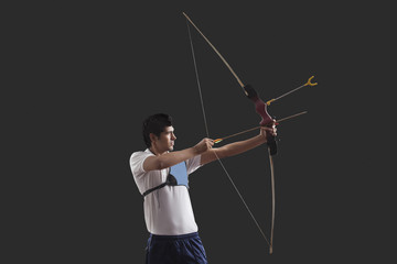 Male archer aiming against black background