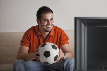 Happy young man with painted face watching television while holding soccer ball