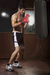 Side view of young man working out with black punching bag at gym