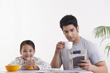 Portrait of happy little girl drinking juice while father reading newspaper