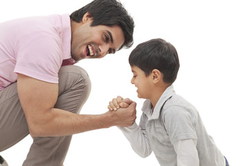 Cheerful father and son arm wrestling over white background