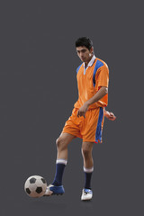 Young Indian male player playing soccer isolated over gray background