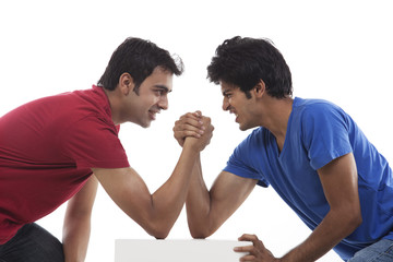 Two young man competing in arm wrestling over white background