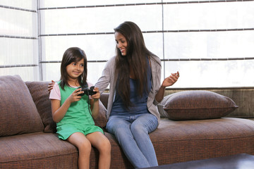 Little girl playing video game while mother looking at her