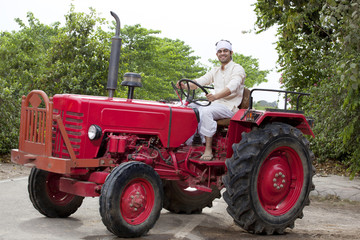 Portrait of a farmer sitting on a tractor smiling