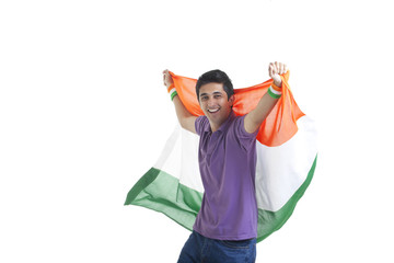 Portrait of happy young man in casual wear holding Indian flag over white background