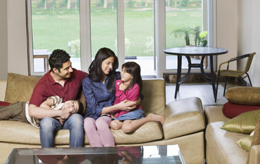 Happy young couple sitting with kids on sofa at home