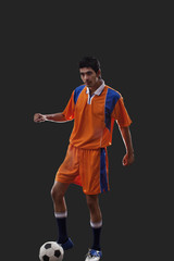 Young male player playing soccer isolated over black background