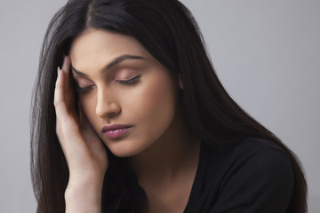 Young Indian female suffering from headache over colored background