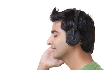 Side view of handsome man listening music over white background