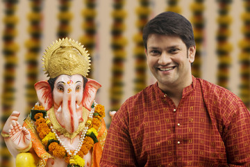 Portrait of a man with a Ganesh idol