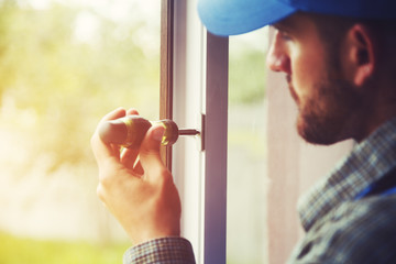 service man installing window with screwdriver