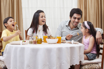 Happy parents and children eating pizza together at restaurant