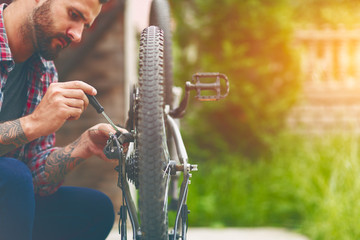 man repairing bike with screwdriver