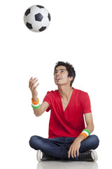 Young boy in casual wear tossing soccer ball while sitting cross-legged over white background