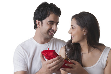 Handsome man gifting bangles to woman against white background