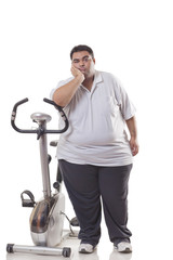 Full length of a tired obese man standing next to an exercise bike over white background