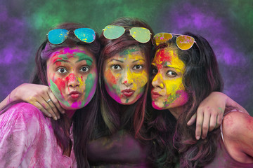 Portrait Of Three Young Indian Women With Colored Face Dancing During Holi Color festival