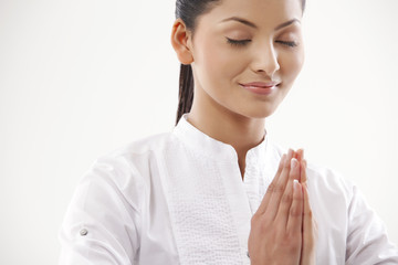 Smiling woman with hands clasped practicing yoga