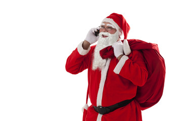 Santa Claus talking on mobile phone while carrying sack over white background