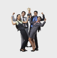 Business executives rejoicing while holding trophy