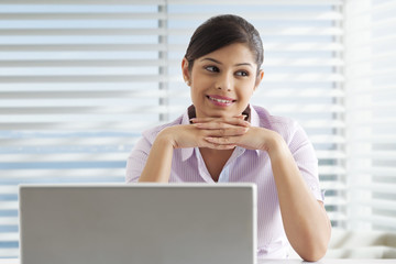 Thoughtful young female executive with laptop at office