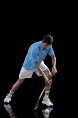 An Indian man in sportswear practicing hockey isolated over black background