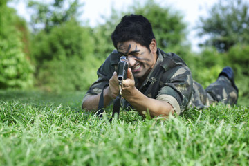 Army soldier aiming with rifle while lying on grass