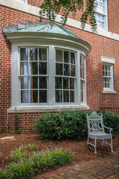 Curved exterior bay window with a metal roof is part of an southern mansion. A white classical iron chair sits in the yard in front of the bay window.