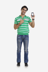 Portrait of young man pointing to mobile phone