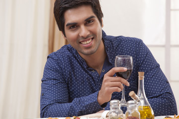Portrait of a young man holding a glass of wine at restaurant