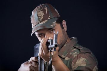 Male soldier aiming gun
