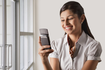 Smiling young businesswoman text messaging at office