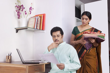 Man working on laptop and woman keeping clothes in cupboard