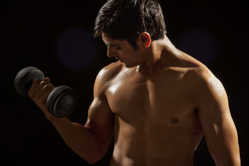 Young man exercising with dumbbell against black background