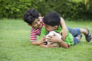 Brothers playing with soccer ball in park