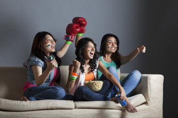 Happy young female friends watching boxing match together at home