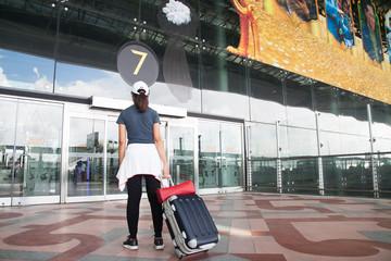 BANGKOK, THAILAND - AUGUST 8, 2017: Asian woman dragging luggage suitcase walking in Suvarnabhumi Airport. Suvarnabhumi Airport is one of beautiful international airport in Asia