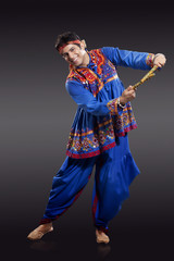 Full length portrait of young man in traditional wear performing Dandiya Raas isolated over black background