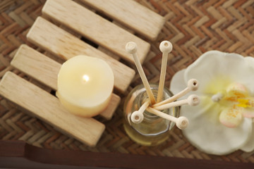 Close-up of reed diffuser with candle and orchid
