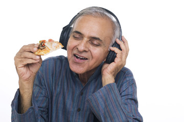 Close-up of senior man eating pizza while listening to music on headphones