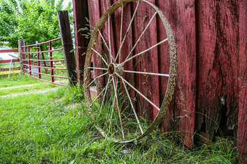 old wagon wheel leaning against a red barn on the farm