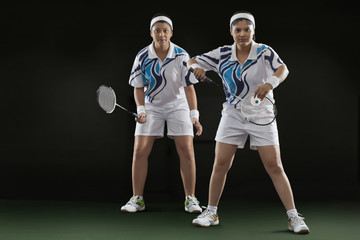 Female partners playing badminton over black background