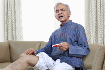 Elderly man applying ointment on knee
