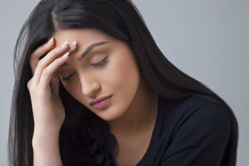 Young Indian woman suffering from headache isolated over colored background